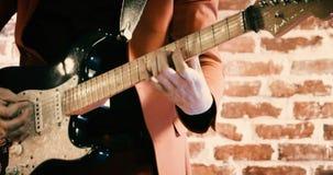 Banda del Rockabilly que toca la guitarra delante de la cantidad defocused de la pared de ladrillo almacen de metraje de vídeo