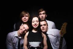 Banda di musica in studio Musicisti e solista della donna che posa sopra il bla Immagine Stock