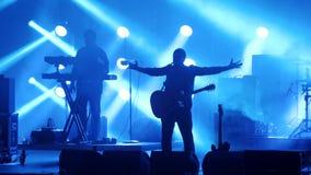Banda rock con la siluetta del chitarrista che esegue su una fase di concerto nel club o nella barra circondata da fumo e dal con video d archivio