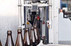 Banda transportadora de una cervecería - botellas de cerveza en la producción y el bott fotos de archivo