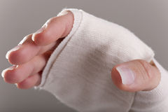 Bandage. Injured Hand with bandage, isolated on gray Stock Photos