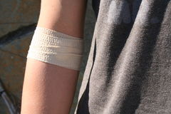Bandage. Teenager with a bandage on his arm after receiving medical care Stock Photos