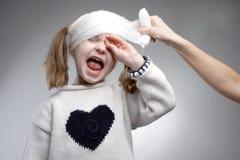 Bandage. Parent applying bandage on little girl forehead Stock Image