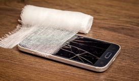 Bandage near the damaged phone. The damaged smartphone needs to be repaired_. Bandage near the damaged phone. The damaged smartphone needs to be repaired stock photos