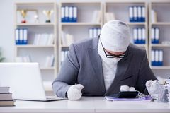 Bandaged businessman worker working in the office doing paperwor Royalty Free Stock Photo