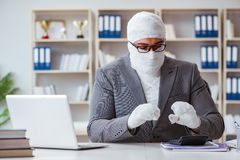 Bandaged businessman worker working in the office doing paperwor. K Royalty Free Stock Image
