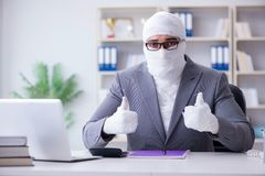 Bandaged businessman worker working in the office doing paperwor. K Royalty Free Stock Photography