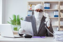 Bandaged businessman worker working in the office doing paperwor. K Royalty Free Stock Photos