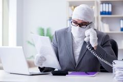 Bandaged businessman worker working in the office doing paperwor. K Stock Images