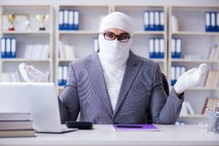 Bandaged businessman worker working in the office doing paperwor. K Stock Photography