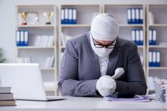 Bandaged businessman worker working in the office doing paperwor. K Royalty Free Stock Images