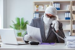 Bandaged businessman worker working in the office doing paperwor. K Stock Photos