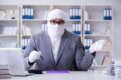 Bandaged businessman worker working in the office doing paperwor. K Stock Photo