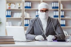 Bandaged businessman worker working in the office doing paperwor. K royalty free stock photo