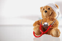 Bandaged Teddy Bear on the Table with Stethoscope Royalty Free Stock Photo