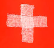 Bandages forming a cross on red background Royalty Free Stock Photo