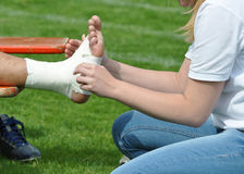 Bandaging an ankle joint. First aid with bandage to a damaged ankle joint Stock Photo