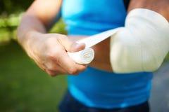 Bandaging arm Royalty Free Stock Photos