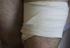 Bandaging an injured knee bandage royalty free stock photo