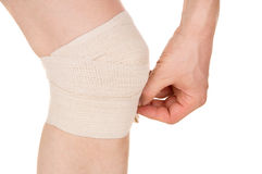 Bandaging the knee with an elastic bandage Royalty Free Stock Image