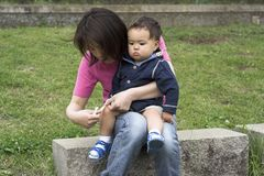 Bandaid. Asian mother putting a bandaid on her sons knee Stock Photo