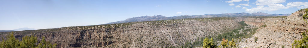 Bandalier panorama one. True wide panorama of Frijoles Canyon, containing Bandalier National Monument, with the Jemez Mountains of central New Mexico in the Royalty Free Stock Photo
