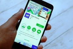 BANDAR SERI BEGAWAN, БРУНЕЙ - 25-ОЕ ИЮЛЯ 2018: Мужская рука держа smartphone с финансами app Yahoo на игре Stor Google андроида стоковые изображения rf
