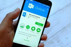 BANDAR SERI BEGAWAN, БРУНЕЙ - 25-ОЕ ИЮЛЯ 2018: Мужская рука держа smartphone с apps Microsoft Outlook на андроиде стоковое фото