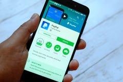 BANDAR SERI BEGAWAN, БРУНЕЙ - 25-ОЕ ИЮЛЯ 2018: Мужская рука держа smartphone с apps Paypal на магазине игры Google андроида стоковое фото rf