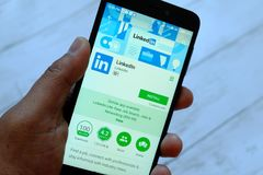 BANDAR SERI BEGAWAN, БРУНЕЙ - 25-ОЕ ИЮЛЯ 2018: Мужская рука держа smartphone с Linkedin app на магазине игры Google андроида стоковая фотография rf