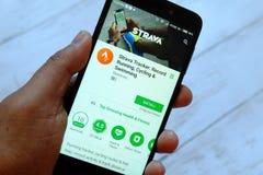 BANDAR SERI BEGAWAN BRUNEI - JULI 25TH, 2018: En hållande smartphone för manlig hand med Strava apps på ett lager för androidGoog royaltyfria bilder