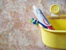 Bandar Seri Begawan/Brunei - Maj 19 2019: Bild av tandborsten och Pepsodent tandkr?m i en gul hink royaltyfri fotografi
