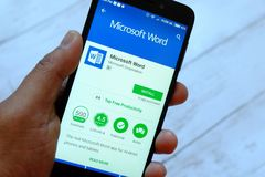 BANDAR SERI BRUNEI, LIPIEC BEGAWAN, - 25TH, 2018: Męski ręki mienia smartphone z Microsoft Word app na androidzie zdjęcie royalty free