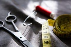 Bande, ciseaux et bobine de mesure jaunes de fil rouge sur le tissu gris Images stock
