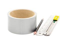 Bande collante avec le crayon de coupeur et règle sur le blanc Photo stock