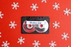 Bande de cassette sonore avec les flocons de neige décoratifs sur un fond rouge Musique pour l'humeur de Noël photographie stock