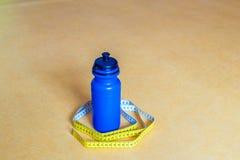 Bande de centimètre, bouteille d'eau sur le fond jaune Mode de vie sain de concept Images stock