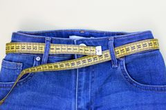 Bande de centimètre comme ceinture dans des jeans plan rapproché, concept de poids de perte Style de vie sain photographie stock