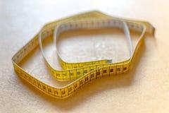 Bande de centimètre se trouvant sur le fond jaune closeup Photo libre de droits