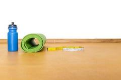 Bande de centimètre, tapis de yoga et bouteille de l'eau au gymnase Images stock