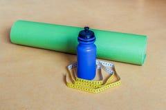 Bande de centimètre, tapis de yoga et bouteille de l'eau au gymnase Photographie stock libre de droits