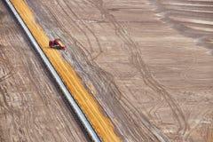 Bande de conveyeur et camion rouge dans le site minier à ciel ouvert de Brown Photographie stock