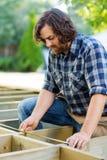 Bande de Measuring Wood With de charpentier à la construction photographie stock