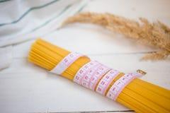 Bande de mesure avec le groupe de spaghetti italiens crus de pâtes, variétés de pâtes Régime, concept sain de nourriture images stock