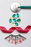 Bande de mesure de stéthoscope de pilules sur des échelles Soins de santé Photos stock