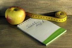 Bande de mesure enroulée autour d'une pomme rouge Photographie stock libre de droits