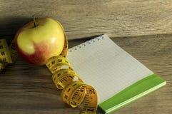 Bande de mesure enroulée autour d'une pomme rouge Image stock
