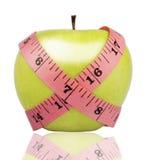 Bande de mesure enroulée autour d'une pomme verte photographie stock