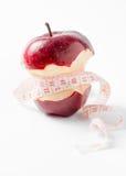 Bande de mesure enroulée autour de la pomme comme symbole de régime Photographie stock libre de droits