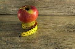 Bande de mesure enroulée autour d'une pomme Photographie stock libre de droits